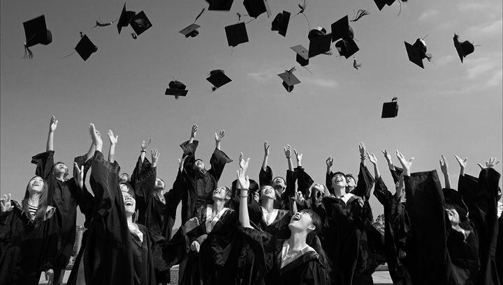 Black & white stock photo of a graduating class in robes throwing their caps in the air