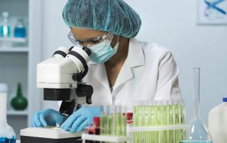 Lab technician looking into microscope.